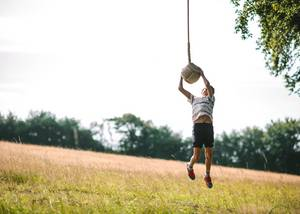 Boy Swinging on Rope Swing