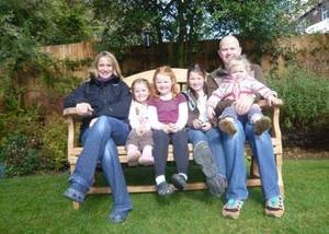 Happy family sitting on a large garden bench