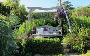 Curved Oak Swing Seat set amongst floral garden