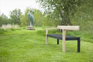 The Floating Bench in scorched and natural oak. Photographed with 'Isis' by Simon Gudgeon at Sculpture by the Lakes