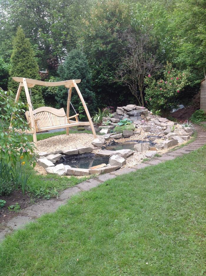 A swing seat in the community garden while the pond was being built