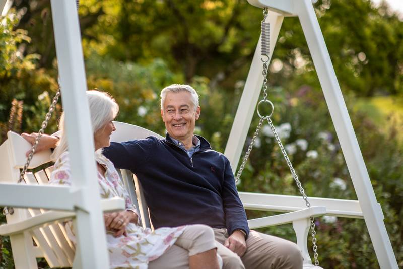 Elderly couple on a painted swing seat in a garden